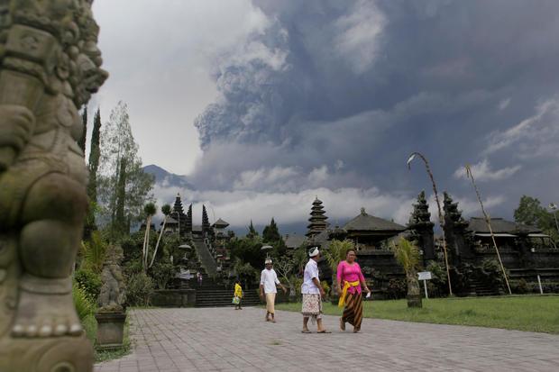 Balinese Hindus walk after praying as Mount Agung volcano erupts at Besakih Temple in Karangasem, Bali